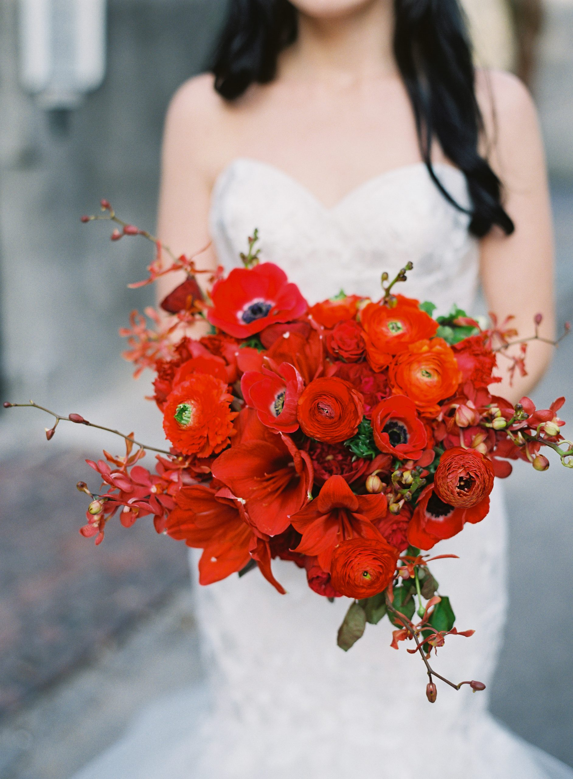 bride holding a red flower bouquet