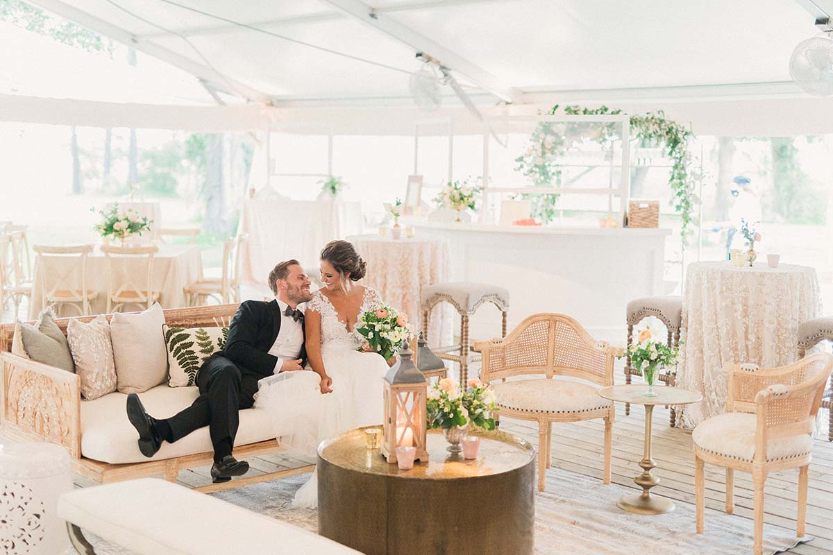 Bride and groom in reception tent decorated in neutral palette with greenery and lots of texture in fabrics